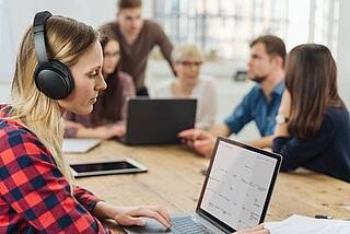 Großraumbüro - Mitarbeiterin schützt sich mit großen schwarzen Kopfhörern vor Bürolärm