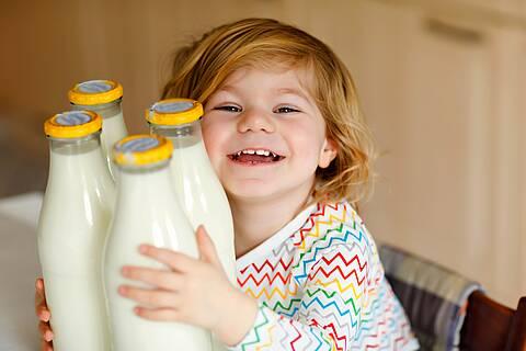 Kind umarmt Glasflaschen mit Milch drin.