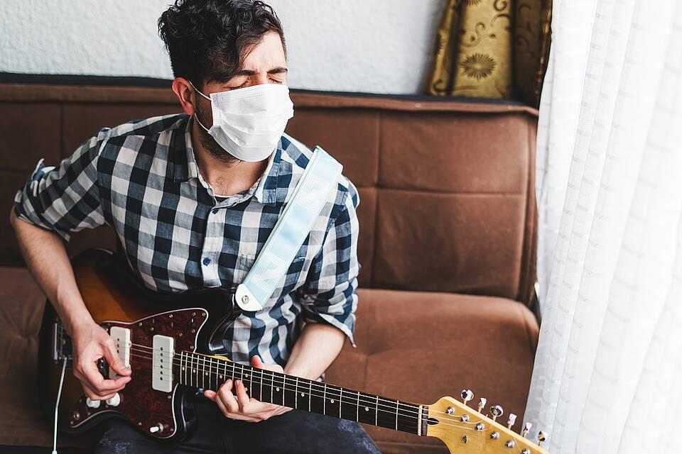 Junger Mann sitzt auf dem Sofa, schließt die Augen und spielt E-Gitarre.