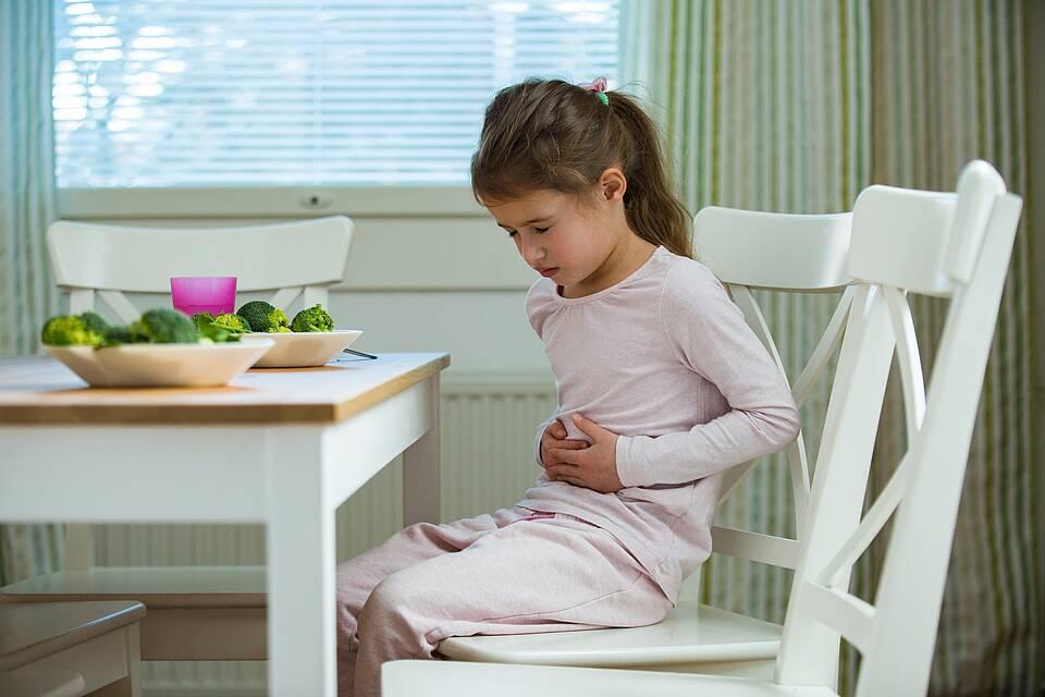 Mädchen hält sich den Bauch wegen Bauchschmerzen.
