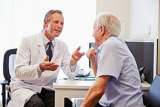 Betriebsarzt spricht mit älterem Mitarbeiter.