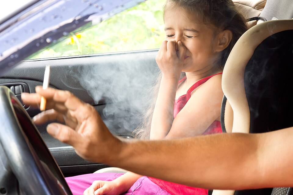 Zigarettenrauch im Auto: Mädchen auf dem Beifahrersitz hält sich angewidert die Nase zu.