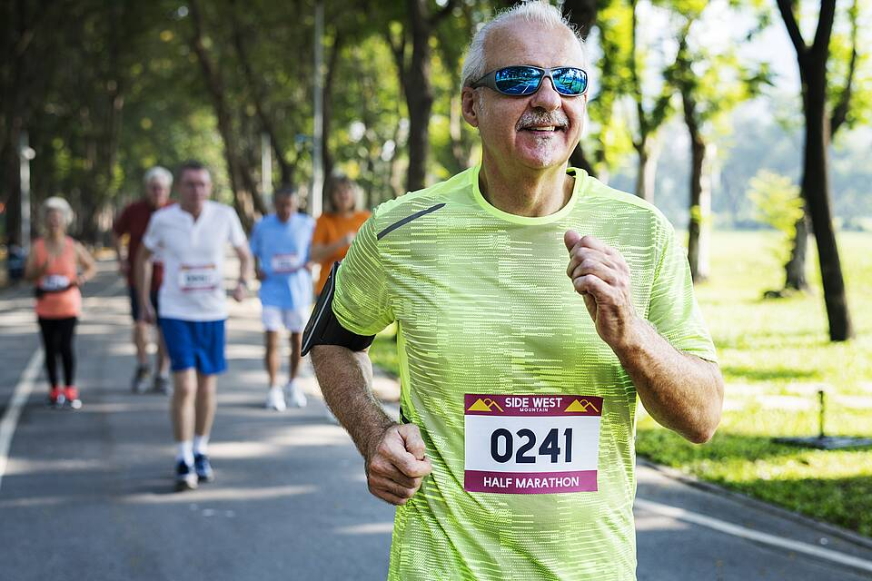 Älterer Mann mit gelben Shirt und blauer Sonnenbrille läuft Halbmarathon.