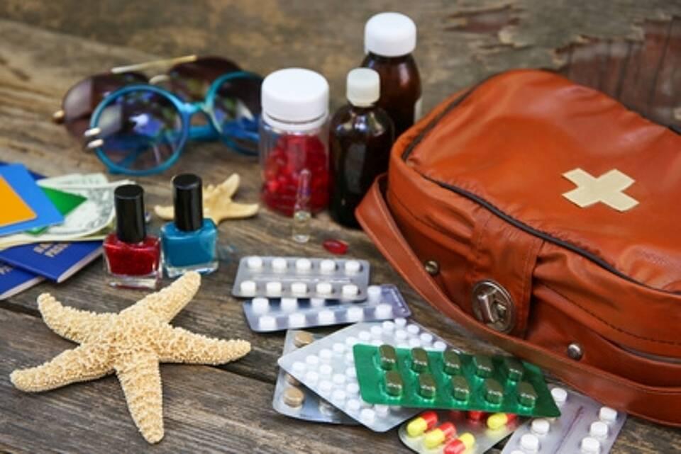 Reiseapotheke: Etui, Tabletten in Blistern, Arzneimittelfläschen, Seestern, Sonnenbrillen