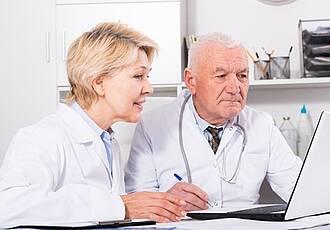 Hausarzt am Schreibtisch in der Praxis