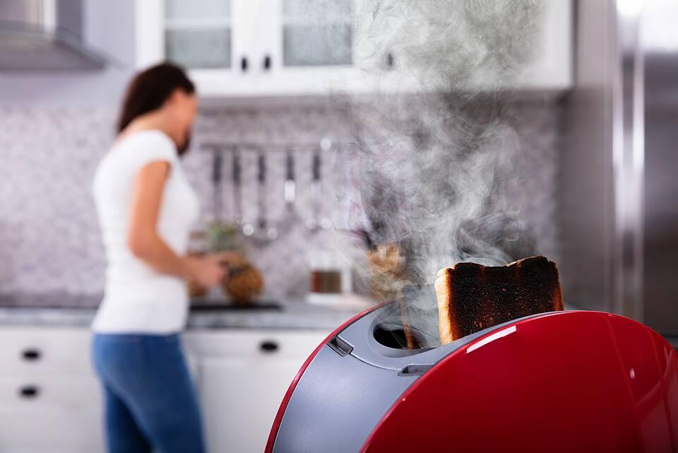 Toaster raucht in der Küche, Frau im Hintergrund