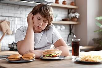 Junge sitzt am Esstisch. Kopf auf die Hand gestützt, grübelt, isst nichts.