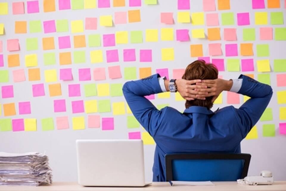 Mann im blauen Jackett im Bürostuhl (Rücken)