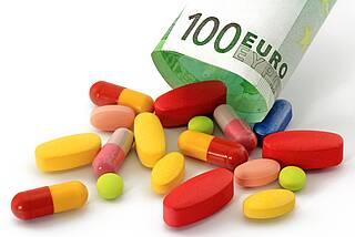 Bunte Pillen fallen aus einem Rohr, das aus einem 100-Euro-Schein geformt ist.