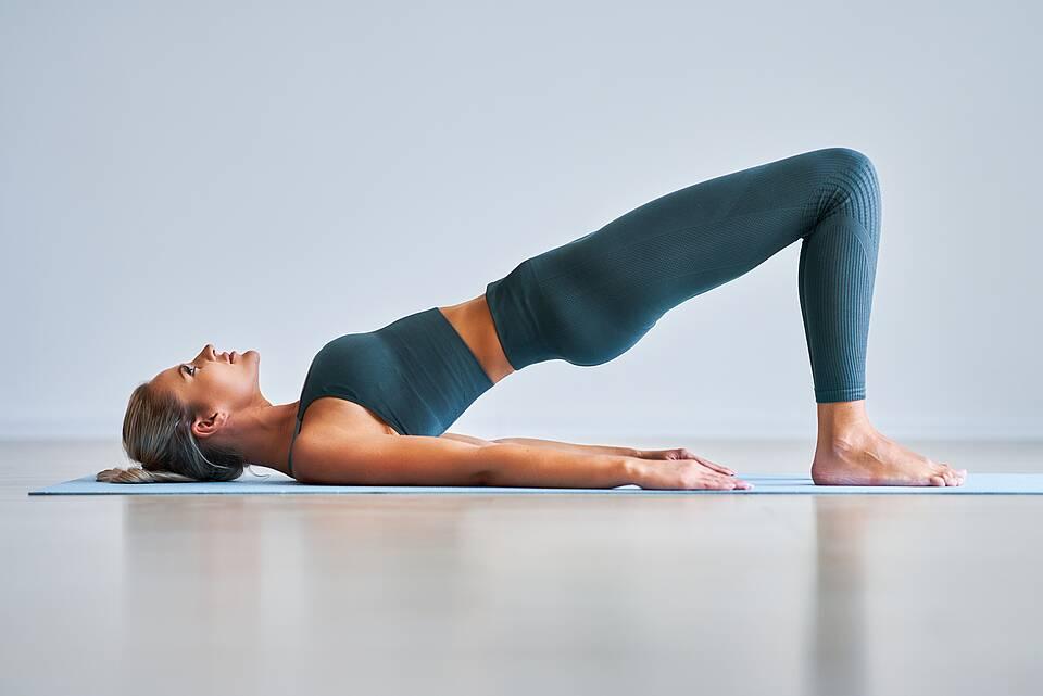 Frau macht Yoga im Liegen.