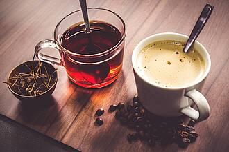 Glas Tee neben Tasse Kaffee, dampfend