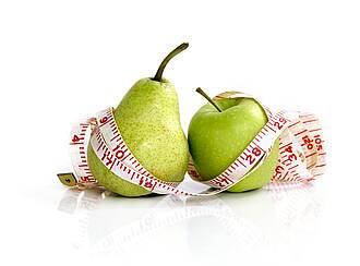 Grüne Birne, grüner Apfel, weißes Maßband mit roter Skala schlängelt sich darum.