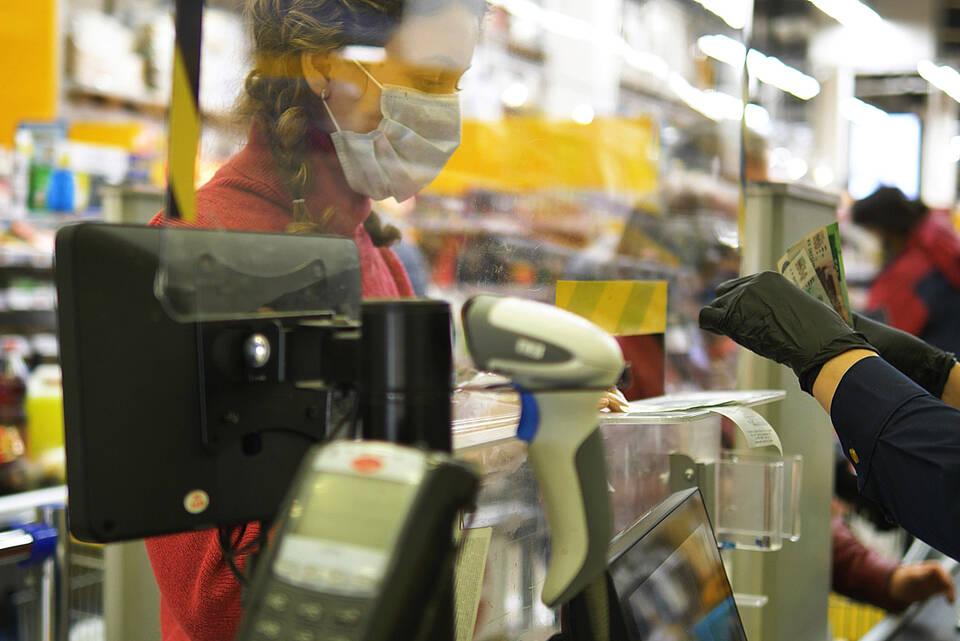 Frau an Ladenkasse mit Corona-Maske hinter Plexiglas-Schutzwand.