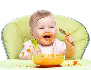 Kleines Kind isst Karottenbrei.