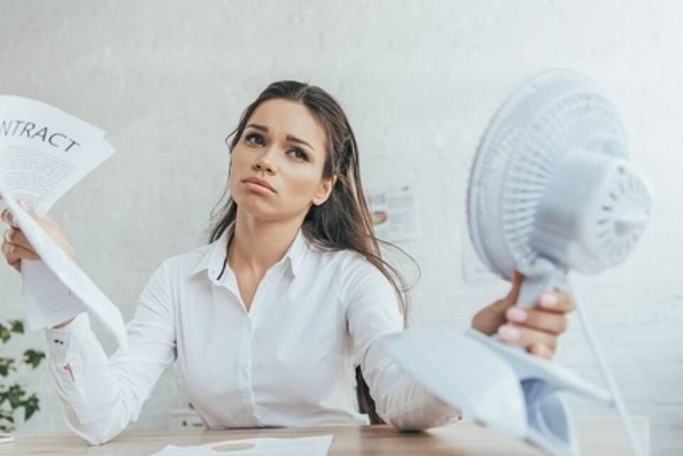 Frau am Schreibtisch hält sich Ventilatro vors Gesicht