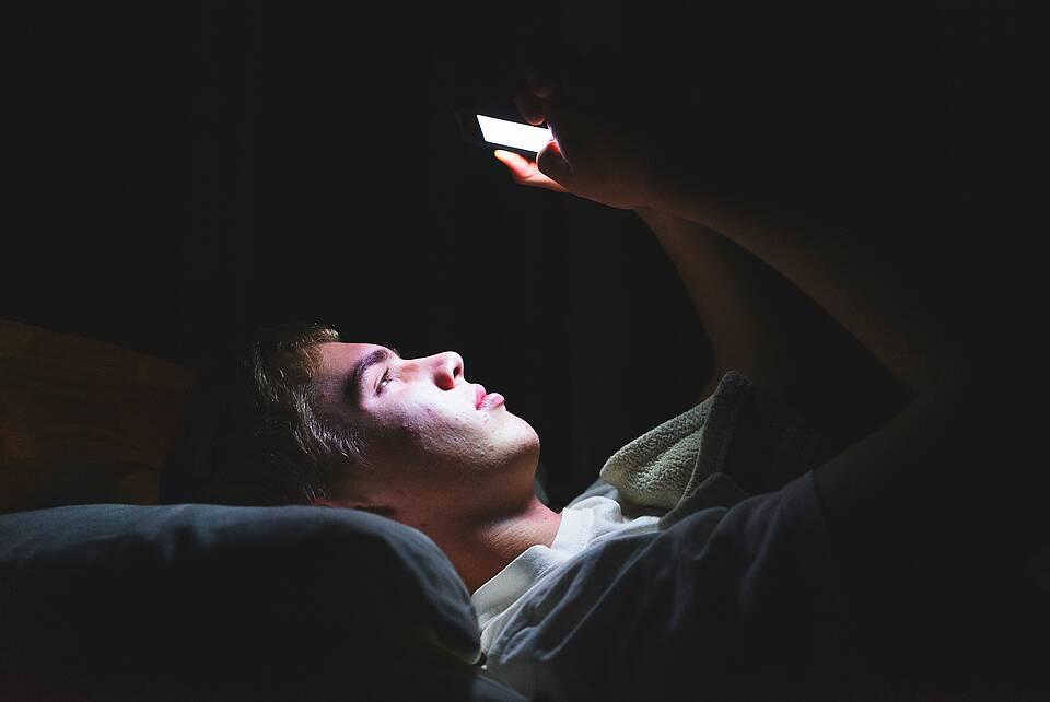 Jugendlicher liegt nachts allein im Bett, im Lichtschein seines Handys.
