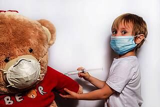 Kleiner Junge impft seinen Teddy-Bären.