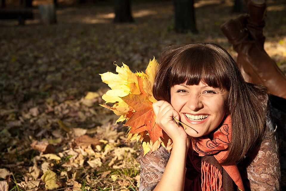 Frau im Herbstwald mit bunten Ahornblättern.