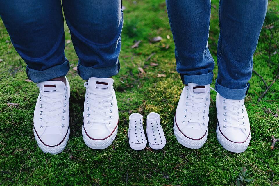 Drei paar Turnschuhe: Mann und Frau mit Füßen drin - Kinderschuhe (noch) ohne.