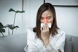 Frau mit verschnupfter Nase und Taschentuch - Nasennebenhöhlen farbig eingezeichnet.