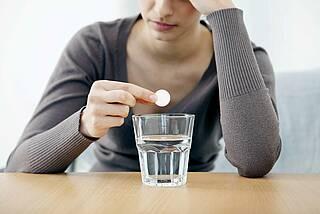 Frau hält schmerzenden Kopf und wirft gleich Brausetablette in ein Wasserglas.