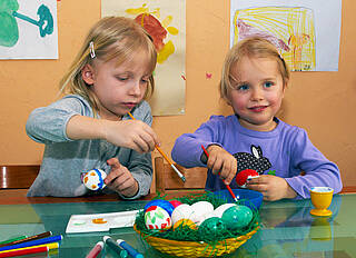 Zwei kleine Kinder bemalen Ostereier