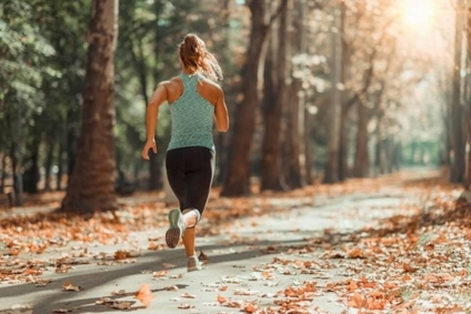 Frau joggt auf Forstweg im Wald durch braunes Laub