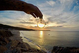 Jemand hält eine Glühbirne vor die untergehende Sonne: optische Täuschung.