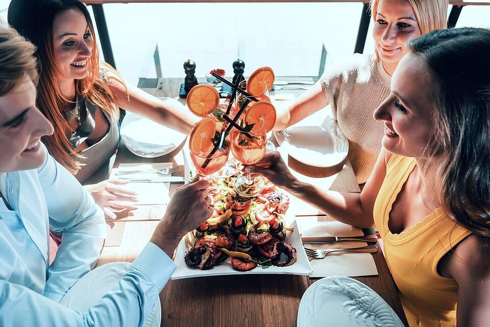 Freunde beim Dinner im Urlaub mit Aperitiv und Meeresfrüchten.