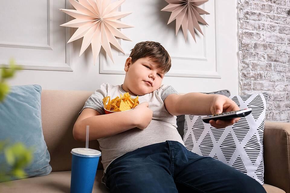 Dicker Junge auf dem Sofa mit Knabbersachen, Cola und Fernbedienung