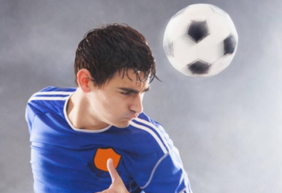 Junger Fußballspieler im blauen Trikot macht Kopfball und schaut grimmig