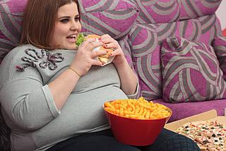Dicke Frau sitzt auf dem Sofa und isst Burger und Flips.