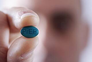 Mann mit blauer Pille in der Hand - Schriftzug PrEP
