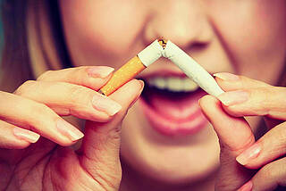 Frau zerknickt Zigarette und lächelt.