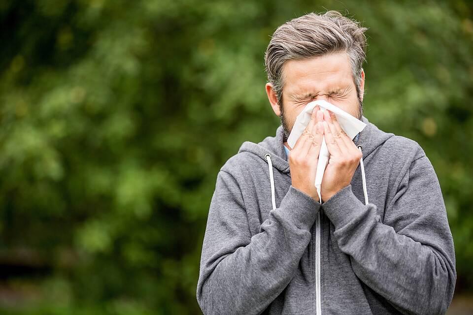 Mann hält sich weißes Taschentuch vors Gesicht und muss niesen.