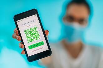Arzt zeigt Smartphone-Display mit Coronatest-Ergebnis