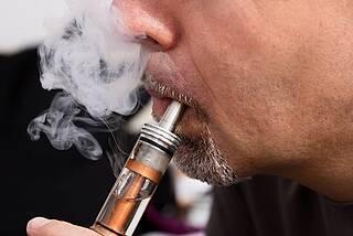 Mann zieht an E-Zigarette, mit Dampfwolke.