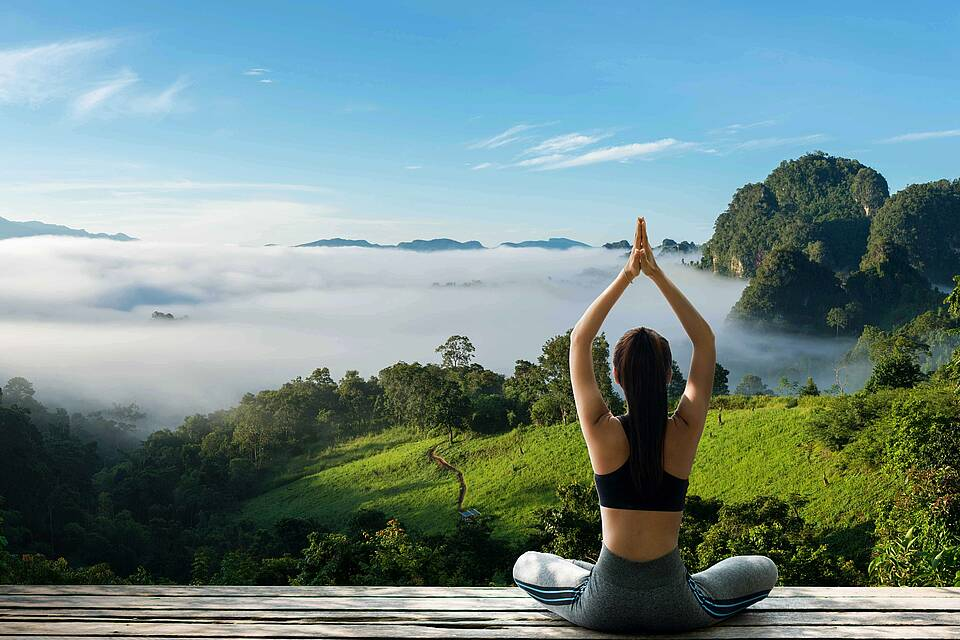 Frau macht Yoga-Übung vor exotischer Natur-Silhouette.