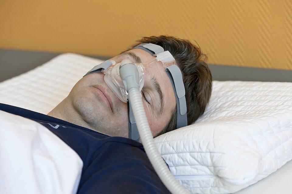 Schlafapnoe: Mann schläft im Bett mit Beatmungsmaske im Gesicht