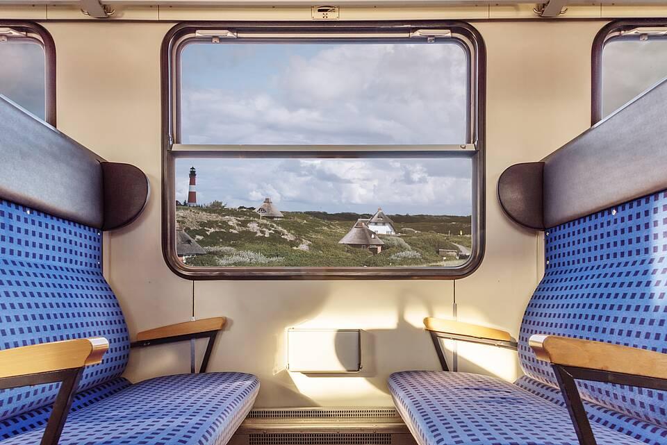 Vierer-Sitzgruppe im Regionalzug, Blick auf norddeutsche Küstenlandschaft