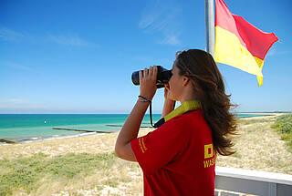Rettungsschwimmerin in roter Sommerkleidung beobachten Badende am Strand mit Fernglas.