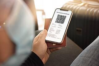 Flugzeugpassagier hält Smartphone mit digitalem Impfnachweis in der Hand.