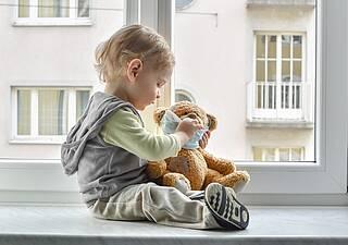 Kleinkind sitzt auf dem Fensterbrett mit Teddybär, der türkisfarbene Coronamaske trägt.
