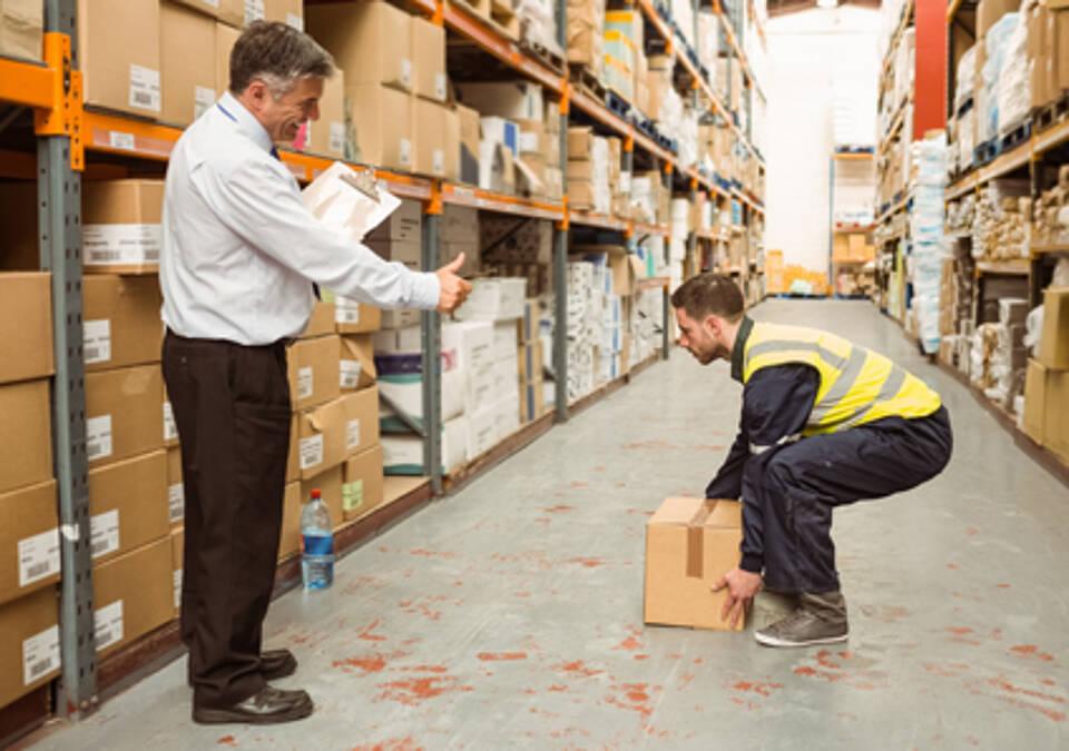 Angestellter zwischen Lagerregalen hebt schwere Kiste an, Chef nimmt den Daumen hoch