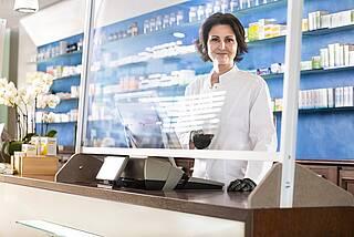 Apothekerin am Tresen hinter Anti-Corona-Plexiglasscheibe.