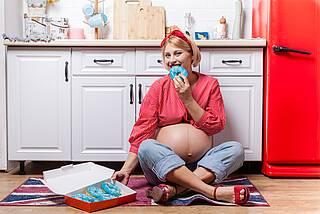 Heißhunger in der Schwangerschaft. Frau isst ganze Schachtel Donuts.