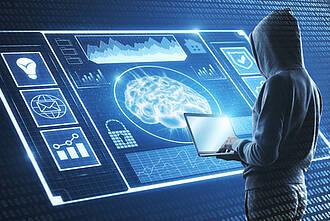 Computer-Hacker, getarnt im Kapuzen-Sweater, mit Laptop vor Diagnosebildern