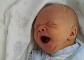 Babykopf im Bett, Kind gähnt