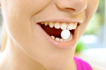 Grinsendes Frauengesicht mit Schmerztablette zwischen den Zähnen